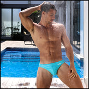 Right side view of an in shape men wearing swimwear in sky blue by the Bang! Clothes brand of men's beachwear from Miami.