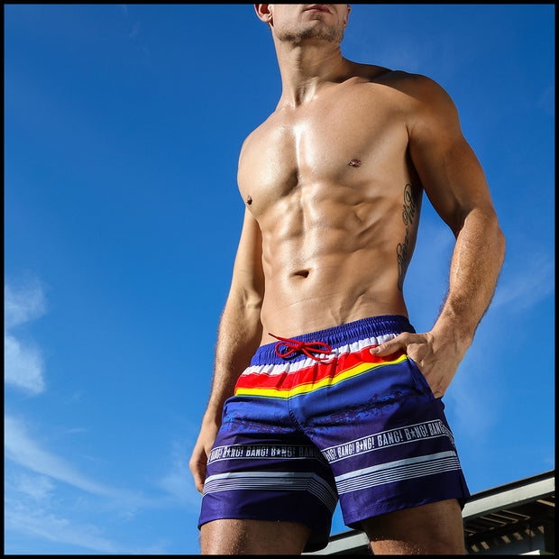Frontal view of a sexy male model wearing men's resort shorts by the Bang! Clothes brand of men&