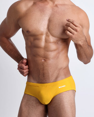 Frontal view of a sexy male model wearing men's swimsuit in yellow by the Bang! Menswear brand from Miami.