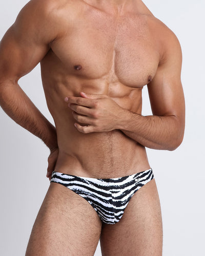 These men's swim mini-brief features an 8-bit print of a sexy zebra with perfect shades of black and white