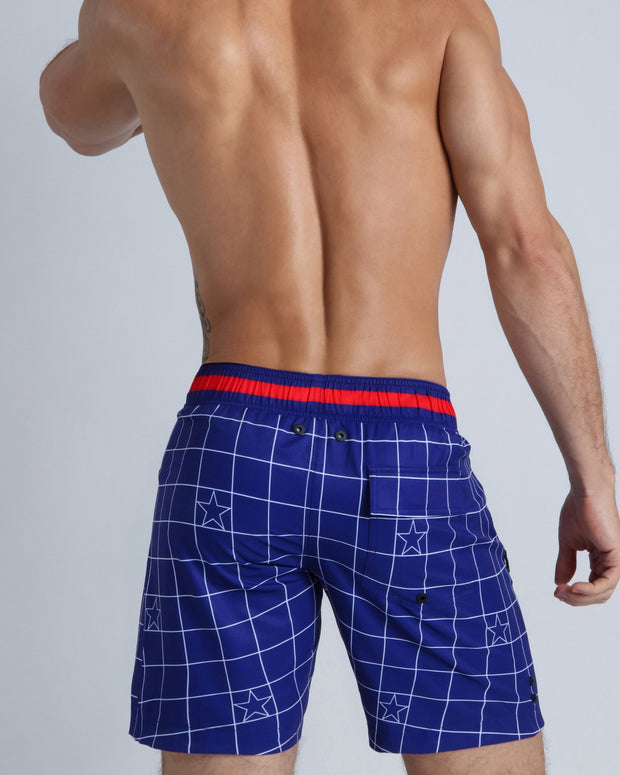Back view of a sexy male model wearing men's beach shorts made by the Bang! official brand of men&