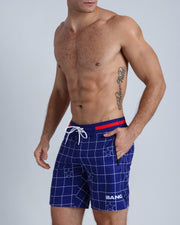 Left side view of  men's boardies in blue color against a grid of white Saleti checkered stripes and white stars.