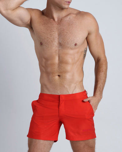 Frontal view of a sexy male model wearing men's beach shorts in bright red by the Bang! Menswear brand from Miami.