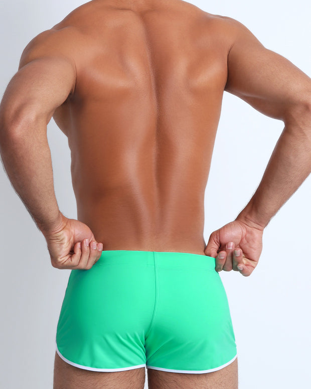 Back view of a male model wearing men's swim brief in red by the Bang! Clothes brand of men&