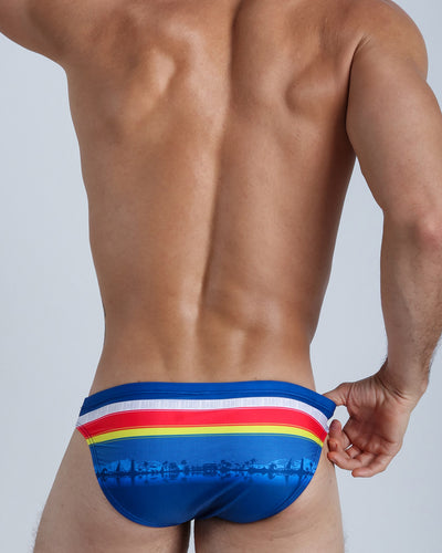 Back side view of a hot male model wearing men's swimwear by Miami-based Bang! Men's beachwear brand.