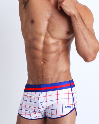 Frontal view of a sexy male model wearing a premium swim short by bang with a grid design form the 80s perfect fit gay mens swimwear