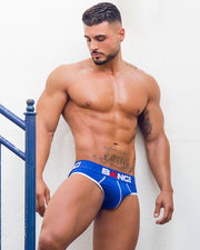 Frontal view of a fit man wearing men's premium cotton brief in blue by the Bang! men's underwear brand from Miami.