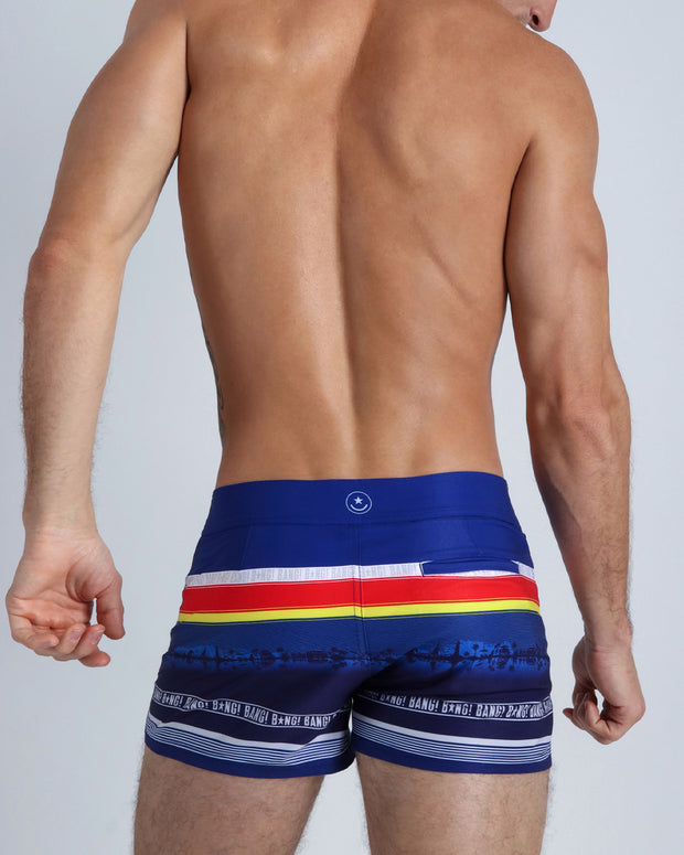 Back side view of a hot male model wearing men's beach trunks by Miami-based Bang! Men&