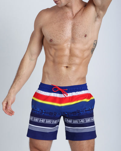 Frontal view of a sexy male model wearing men's resort shorts by the Bang! Clothes brand of men's beachwear from Miami.