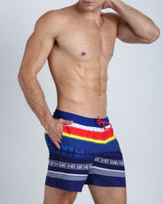 These men's boardies show a silhouette of a beachside town in blue backgrond with stripes in yellow, red, and white.