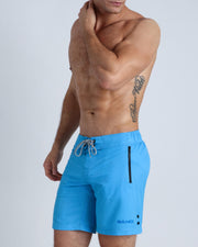 Left side view of a masculine model wearing men's flex boardshorts in blue color with official logo of BANG! Brand.