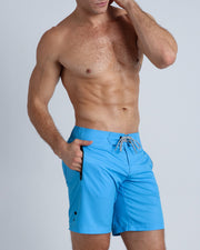 Right side view of an in shape men wearing board shorts in blue color by the Bang! brand of men's beachwear from Miami.