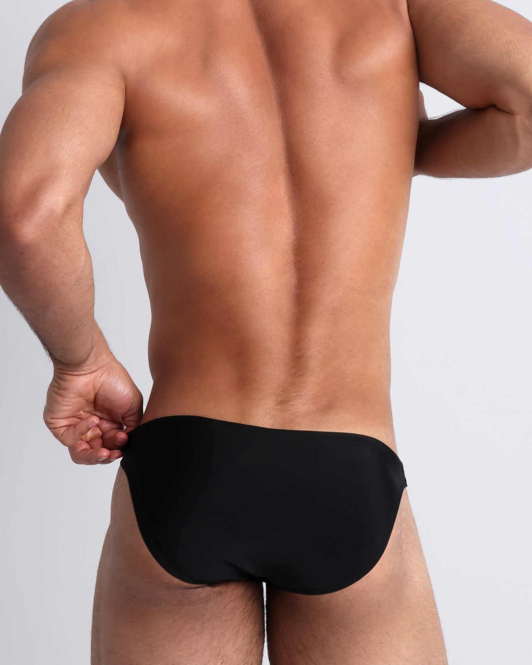 Frontal view of a sexy male model wearing men's swimsuit in black by the Bang! Menswear brand from Miami.
