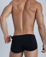 Back view of a male model wearing men's swim shorts in black by the Bang! Clothes brand of men's beachwear from Miami.