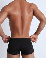 Back view of a male model wearing men's swim brief in black by the Bang! Clothes brand of men's beachwear from Miami.