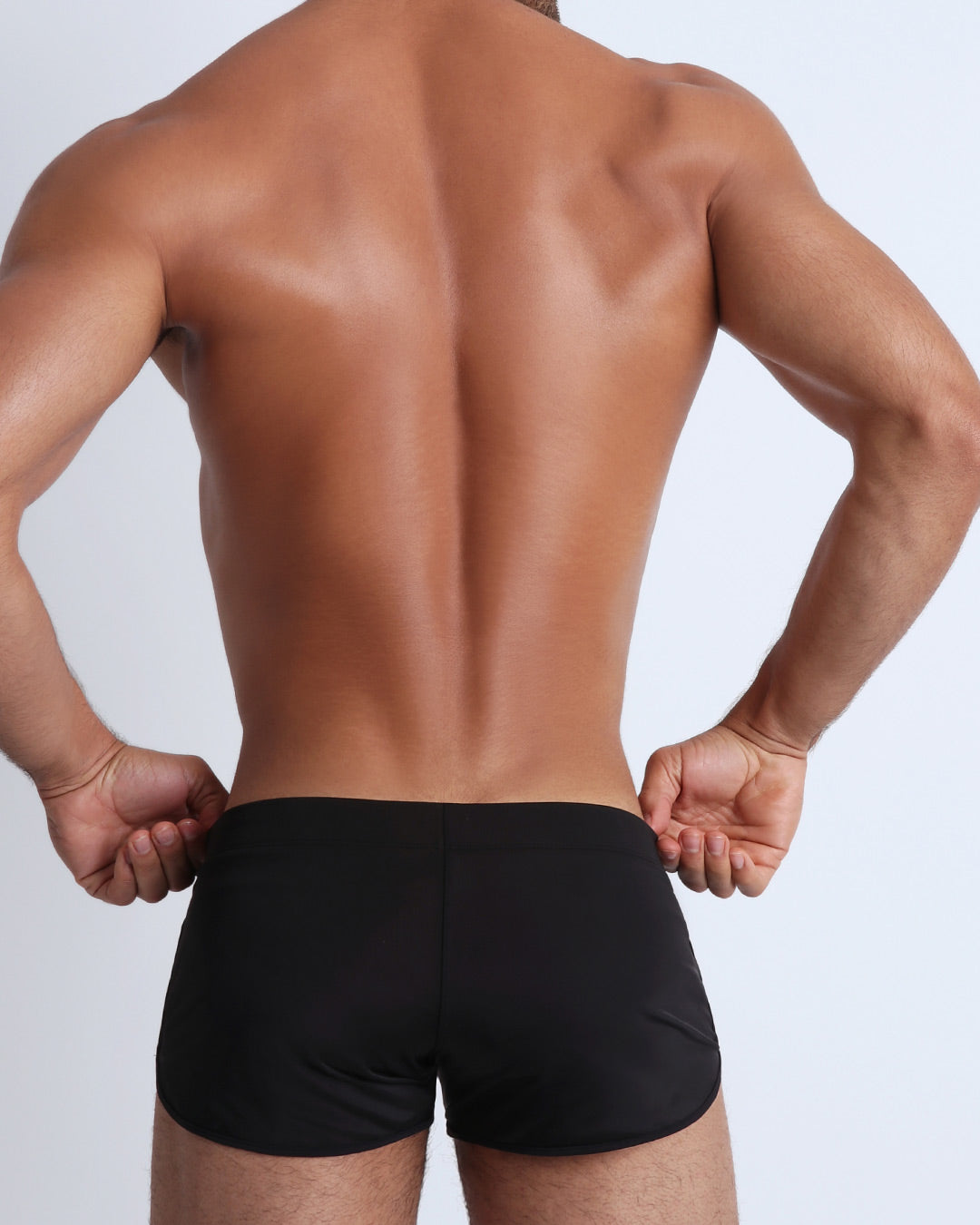 Left side view of a masculine model wearing men's swim shorts in solid black with official logo of BANG! Brand in white.