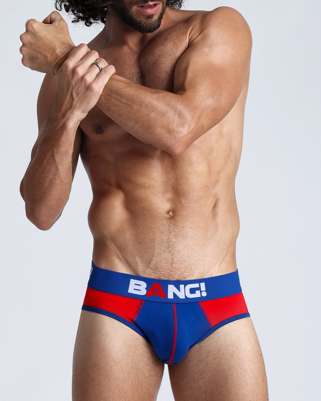 Frontal view of a sexy guy wearing a men's premium cotton brief in red and blue by the Bang! brand.