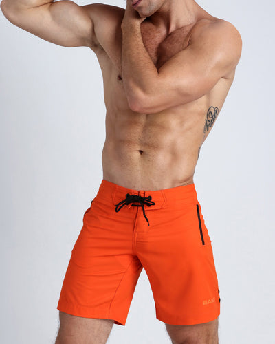Frontal view of a sexy male model wearing men's boardshorts in orange color by the Bang! Menswear brand from Miami.
