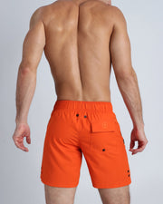 Back view of a male model wearing men's boardies in solid orange color by the Bang! brand of men's beachwear from Miami.