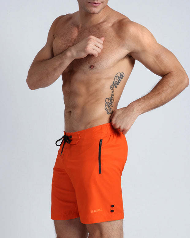 Left side view of a masculine model wearing men's flex boardshorts in orange color with BANG! Brand logo.