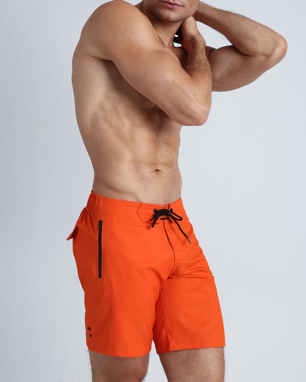 Right side view of an in shape men wearing board shorts in orange color by the Bang! brand of men&