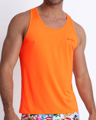 Frontal view of a sexy male model wearing a men's tank top in a beautiful orange color by the Bang! Menswear brand from Miami.