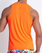 Back view of a male model wearing a men's tank top in a beautiful orange color by the Bang! Clothes brand of men's beachwear from Miami.