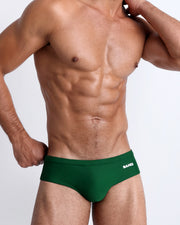 Frontal view of a sexy male model wearing men's swimsuit in green by the Bang! Menswear brand from Miami.