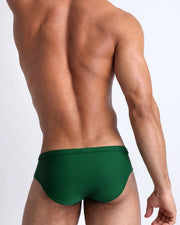 Back view of a male model wearing men's swim brief in green by the Bang! Clothes brand of men's beachwear from Miami.