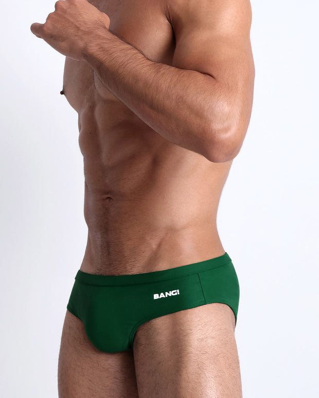 Left side view of a masculine model wearing men's swimsuit in solid green with official logo of BANG! Brand in white.