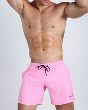 Frontal view of a sexy male model wearing men's boardshorts in pink by the Bang! Menswear brand from Miami.