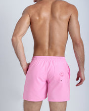 Back view of a hot male model wearing men's boardshorts in pink by the Bang! Clothes brand of men's beachwear from Miami.