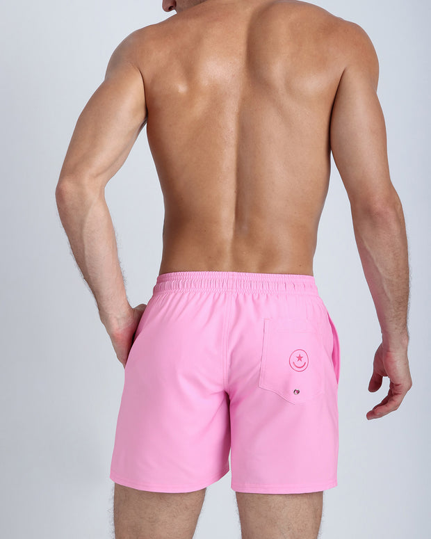 Back view of a hot male model wearing men's boardshorts in pink by the Bang! Clothes brand of men&