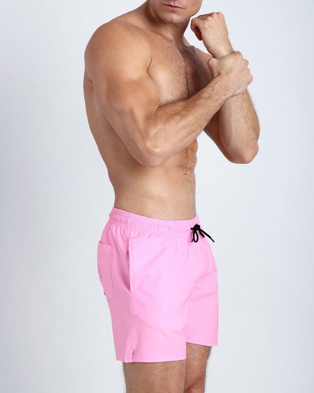 Right side view of an in shape men wearing boardshorts in pink by the Bang! Clothes brand of men&