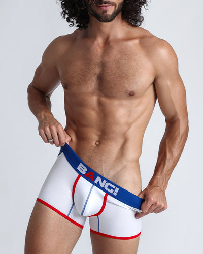 Frontal view of a sexy model wearing a white cotton boxer brief with read and blue details, by Bang! underwear for men.