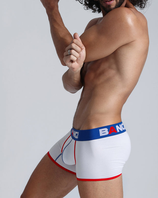 Left side view of a hot guy wearing a cotton boxer brief for men in white with red and blue accents by Bang! Men&