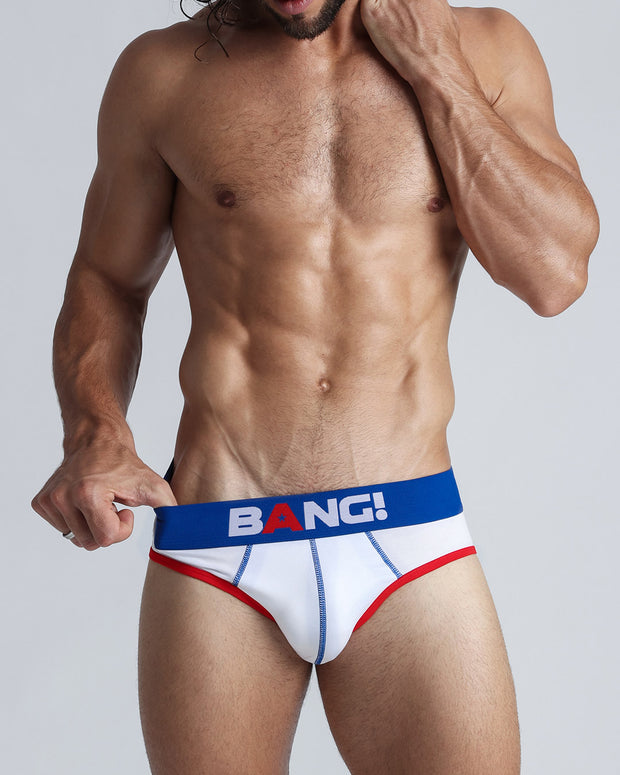 Frontal view of a sexy model wearing a white cotton brief with read and blue details, by Bang! underwear for men.