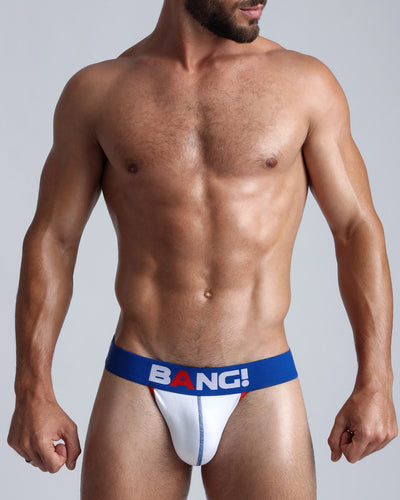Frontal view of a sexy model wearing a white cotton Jockstrap with read and blue details, by Bang! underwear for men.