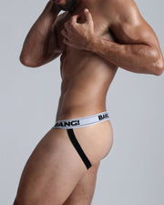 Left side view of male model in men's black jockstrap by the Bang! men's underwear brand from Miami.