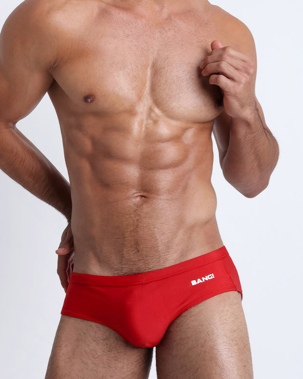 Frontal view of a sexy male model wearing men's swimsuit in red by the Bang! Menswear brand from Miami.