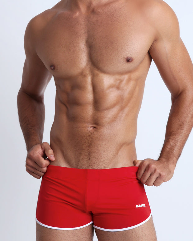 Left side view of a masculine model wearing men's swimsuit in solid red with official logo of BANG! Brand in white.