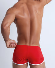 Back view of a male model wearing men's swim brief in red by the Bang! Clothes brand of men's beachwear from Miami.