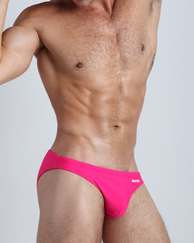 Right side view of an in shape men wearing swimwear in barbie pink color by the Bang! brand of men&