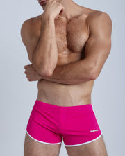 Frontal view of a sexy male model wearing men's swimsuit in magenta pink by the Bang! Menswear brand from Miami.