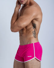 Left side view of a masculine model wearing men's swimsuit in hot pink with official logo of BANG! Brand in white.