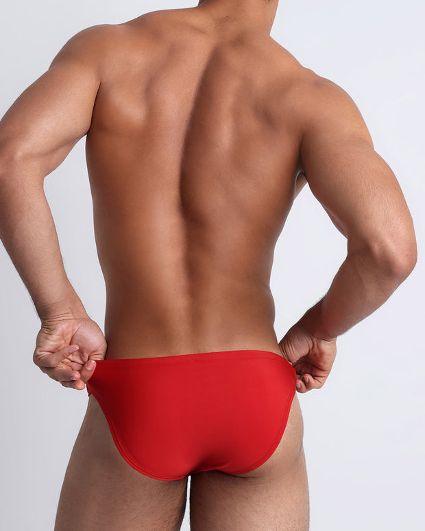 Back view of a male model wearing men's swim mini-brief in red by the Bang! Clothes brand of men&