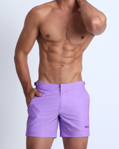 Frontal view of a sexy male model wearing men's tailored shorts in a light violet color by the Bang! Menswear brand from Miami.