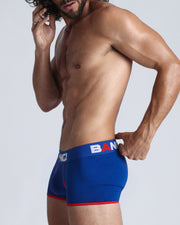 Left view of a sexy model wearing a blue cotton boxer brief for men by the Bang! menswear brand from Miami.