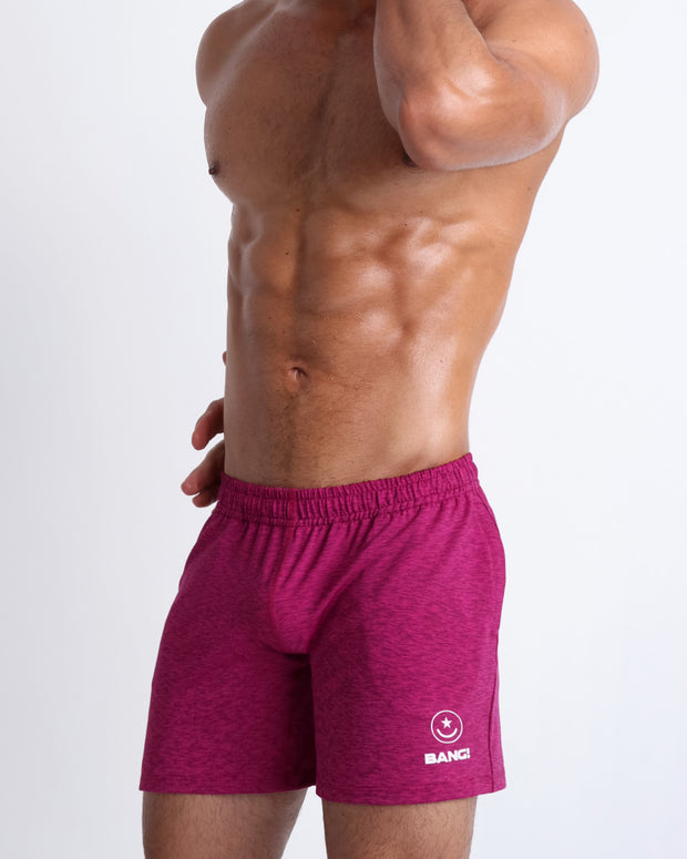 Right side view of model wearing men's sport shorts endowed with the form-fitting shape of a tight jogger for gym.