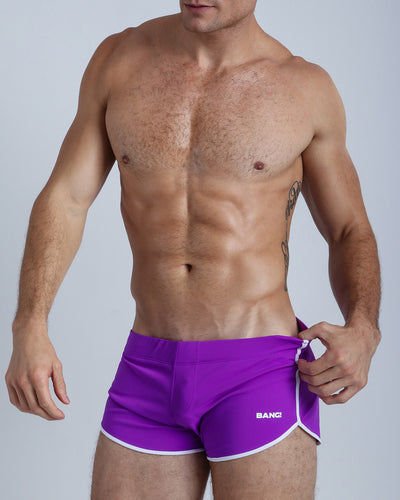 Left side view of a masculine model wearing men's swimsuit in solid purple with official logo of BANG! Brand in white.
